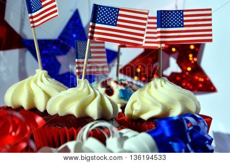 Happy Independence Day celebration patriotism and holidays concept - close up of glazed cupcakes or muffins decorated with american flags at 4th july party