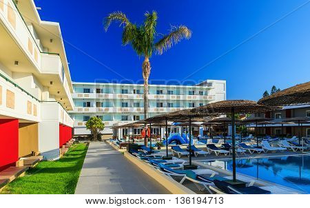 courtyard of a modern hotel with a pool and sunbeds