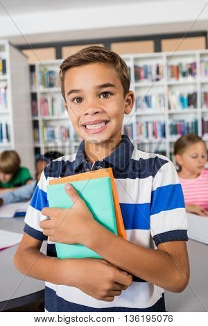Little boy standing with notebooks in library