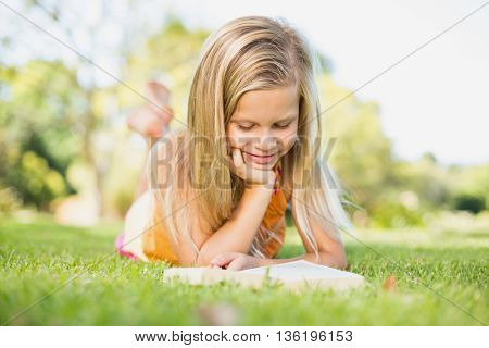 Young girl lying on grass and reading book in park