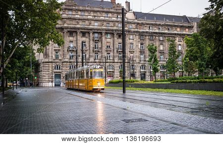 Budapest, Hungary - July 07, 2015: traditional yellow hungarian tram in the square near Hungarian Parliament in Budapest