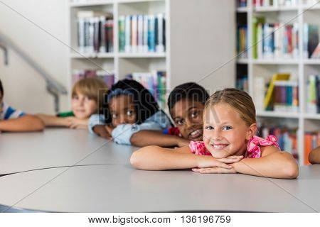 Pupils posing for the camera at desk in the library