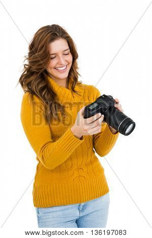 Young woman using camera on white background