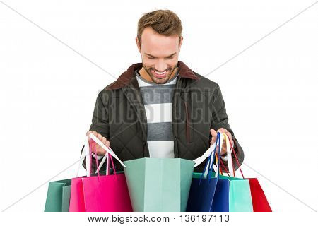Young man with shopping bags on white background