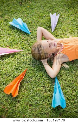 Happy young girl lying on grass around paper planes in park
