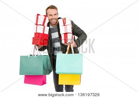 Happy young man holding gifts and shopping bags on white background