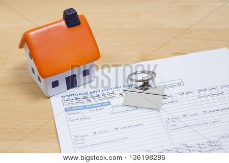 Mortgage application paper work with foam house and key ring