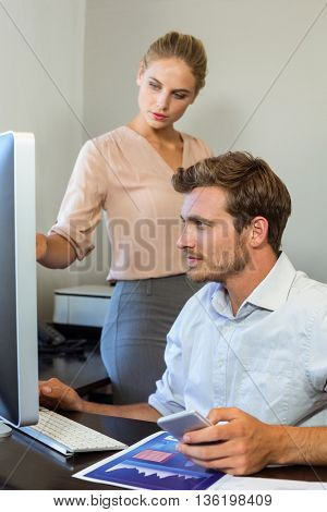Young colleagues working on computer at desk in office