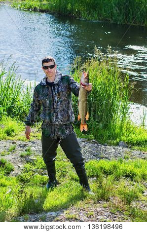 Fisherman in sunglasses stands on the banks of the river and holds in his hand pike