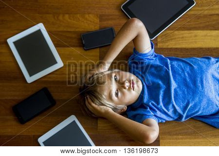Little boy sad, tired and stressed with tablet computer PC. Kid holding his head. Digital tablets, mobile phones, laptop all around. Top view. Education, learning, technology concept