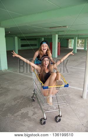Cheerful blonde girl riding shopping cart with brunette sitting in and showing peace signs