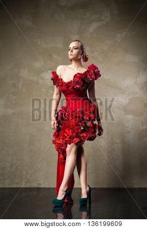 Portrait of blonde model with hairstyle and make-up in beautiful red dress decorated with flowers
