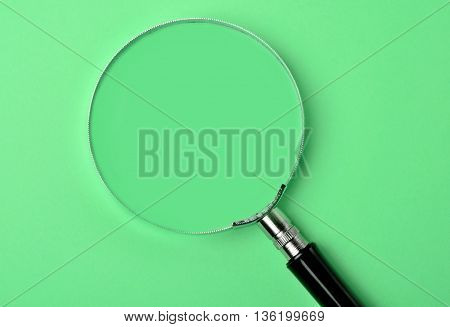 Magnifying glass on green background close up