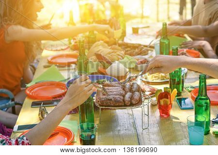 Group of multiracial students having barbecue on a sunny day - Young cheerful people eating meat on summer time - Concept about good and positive mood with friends - Soft focus on sausages