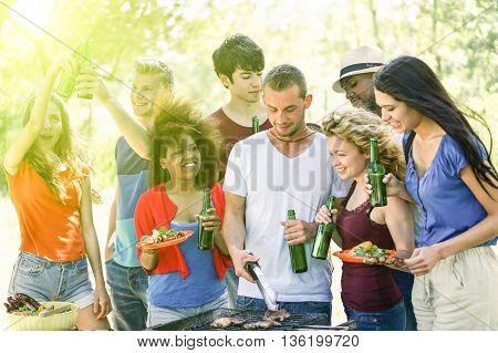 Happy friends in the park having barbecue on a sunny day - Group of multi ethnic people eating and drinking outdoor - Concept about good and positive mood with friends - Soft focus on black girl