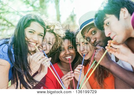 Group of multi race friends enjoying drink outdoor summer party - Multi ethnic students having fun with back lighting - Friendship and party concept - Soft focus on black girl