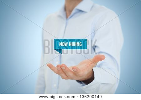 Businessman (recruiter or HR staffer) hold virtual label with text now hiring - human resources concept..