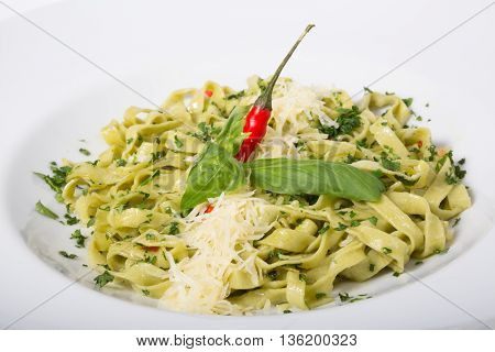 Green italian tagliatelle pasta with cheese and basil