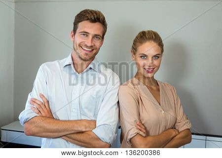 Happy man and woman standing against wall at office