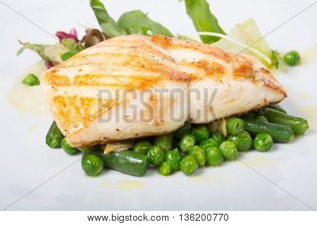 Fried white fish fillet with peas garnish