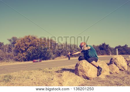 The bearded smiling man wearing in sunglasses having fun next to the road sitting on a rock pretending that he was going ride on a motorcycle and lays the bend. Travel it is fun. Toned image.