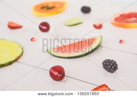 Minimal composition of tropical and european fruits - Mix of summer colored fruits on wood background - Healthy lifestyle concept - Vintage retro filter with focus on cherry