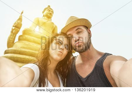 A just married couple making selfie self portrait using mobile phone next Buddha statue in Thailand - Young people having fun with new trends technology - Soft focus on faces with vintage retro filter