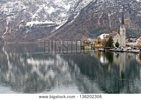 Hallstatt Austria - April 10 2012: Light and reflection of Hallstat Lutheran Church and lake