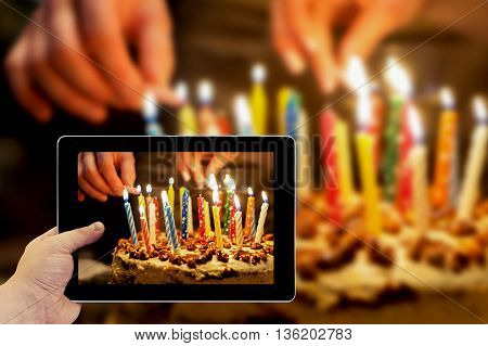Tablet Photography Concept. Taking Pictures On A Tablet. Birthday Cake With Burning Candles In The D