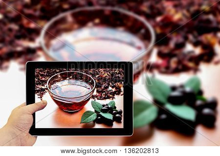 Tablet Photography Concept. Taking Pictures On A Tablet. Still Life Cup Of Black Tea With Mint Leave