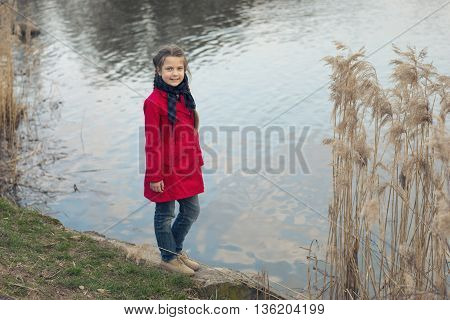 girl in red fashion raincoat on the river shore with dry reed stalks around