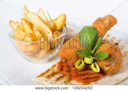 Fried chicken legs served with potatoes and pita flat bread