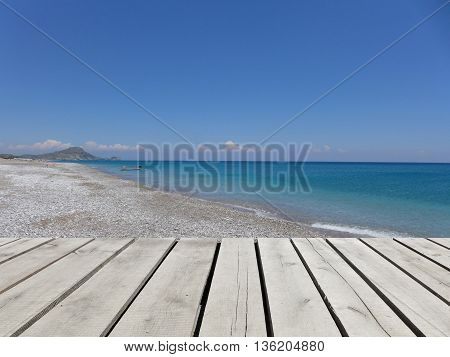 Wooden pier with blue sea sky and white pebble beach background. Mediterranean landscape in sunny day. Greek island. Vacation concept. Afandou beach Rhodos Greece Europe. Scenic view.