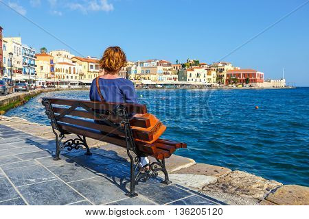 Young Woman Sitting On The  Bench And Looking At Old Port In Chania, Crete, Greece