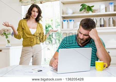 Woman arguing with upset man in kitchen at home