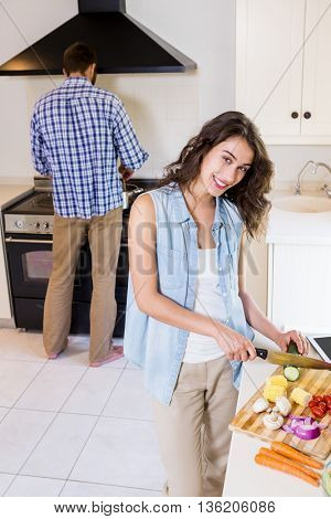 Woman chopping vegetables and man cooking on stove in kitchen at home