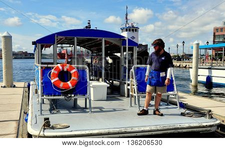 Baltimore Maryland - July 22 2013: Crew member standing on the deck of a Red Line Water Taxi docked at the Fells Point landing slip
