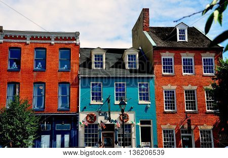 Baltimore Maryland - July 22 2013: 18th and 19th century brick buildings lining the historicThames Street waterfront now house trendy shops pubs and restaurants at Fells Point