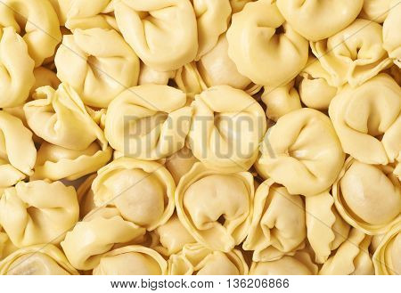 Surface covered with ravioli dumplings, close-up fragment crop as a backdrop composition