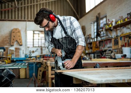 Carpenter working on his craft in a dusty workshop