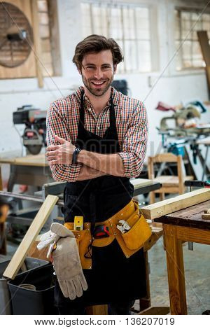 Carpenter is posing with his craft in a dusty workshop