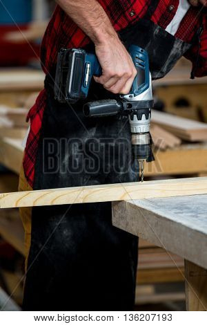 Carpenter using a drill in his workshop