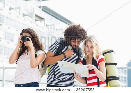 Woman clicking photo while her friends looking at map on terrace