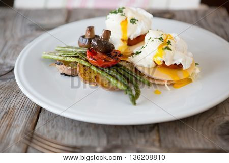 Benedict eggs with grilled asparagus, mushrooms and potatoes