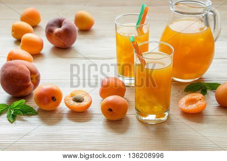 Right apricot peach juice in glasses with ice near the jar of juice and scattered apricots peaches mint left empty space on a light wooden background. Apricot and peach juice with ice. Horizontal.