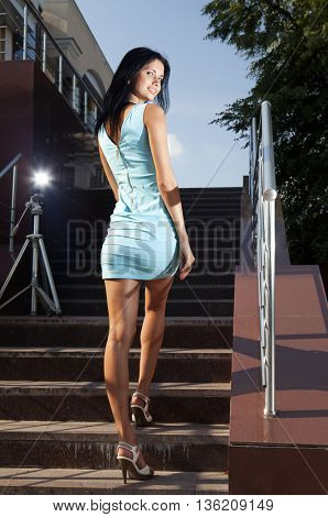 beautiful brunette in blue dress goes on steps