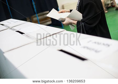 A person prepares to cast a ballot at a polling station during voting.