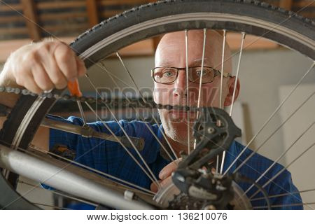a man repairing bicycle in his workshop.