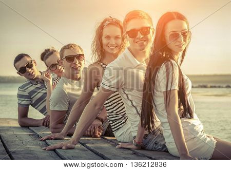 Friends sitting on wooden pier under sunset light.