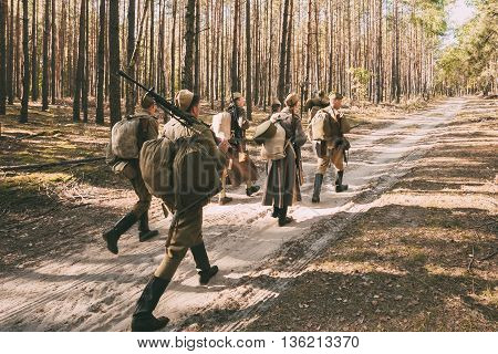Teryuha, Belarus - October 3, 2015: Group of unidentified re-enactors dressed as Soviet russian soldiers goes along forest road.